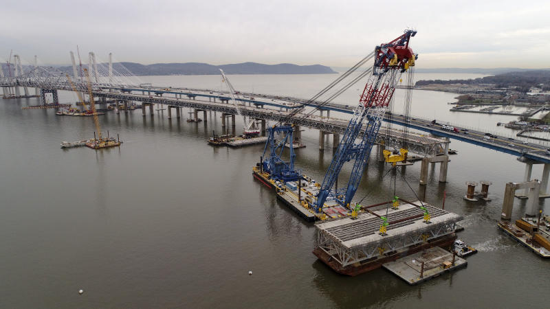 In this Saturday, Nov. 18, 2017, photo, a section of the Tappan Zee Bridge is lowered by floating crane onto a barge on the east end of the bridge, in Tarrytown, N.Y. More than a hundred 50-foot long deck panels, already removed from the sections during the ongoing demolition, will be repurposed for use on bridges in several state and local municipalities. (AP Photo/Julie Jacobson)