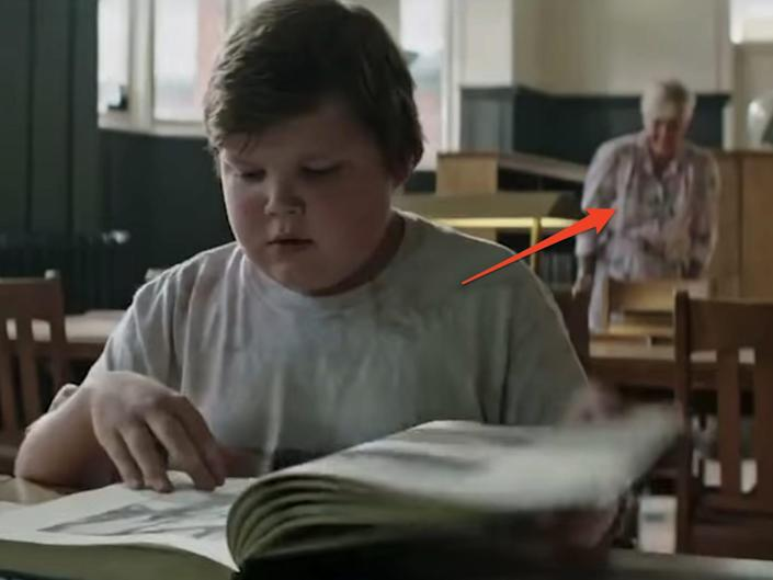 """a boy reading at a library with an older woman blurred out in the background in """"It."""""""