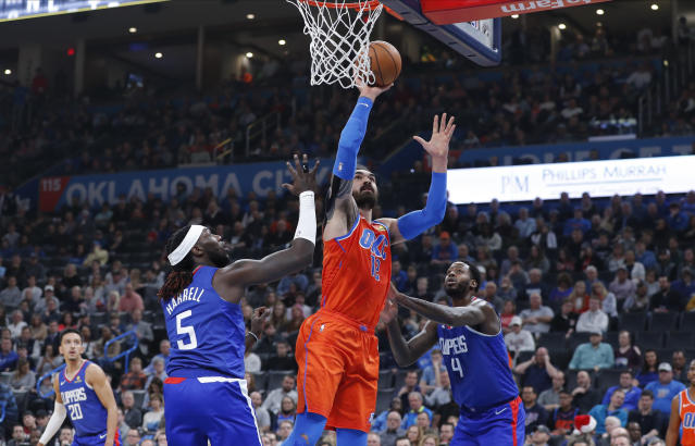 Oklahoma City Thunder center Steven Adams (12) goes up for a basket between Los Angeles Clippers forward Montrezl Harrell (5) and forward JaMychal Green (4) during the second quarter of an NBA basketball game Sunday, Dec. 22, 2019, in Oklahoma City. (AP Photo/Alonzo Adams)