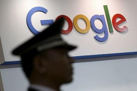 A security guard keeps watch as he walks past a logo of Google at an exhibition stage during the 4th China (Shanghai) International Technology Fair 2016 in Shanghai,