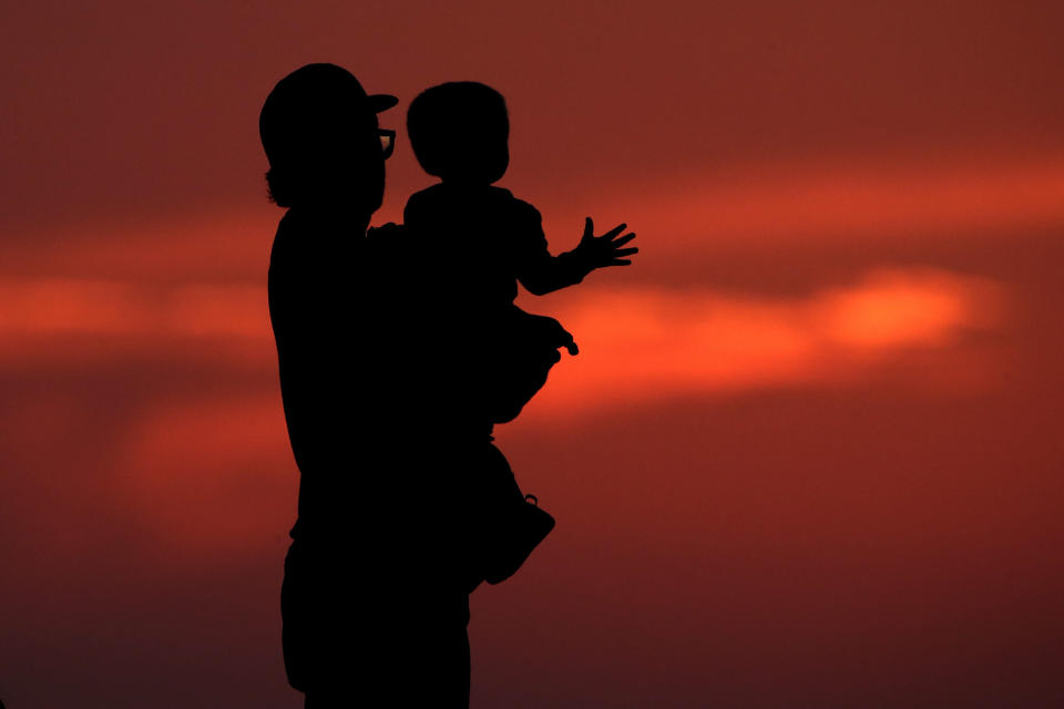 FILE - This photo from Friday June 26, 2020, shows a silhouette against the sky of a man holding a child, as they watch the sunset from a park in Kansas City, Mo. The chaos unleashed in 2020, amid the coronavirus pandemic, has created space for different voices to speak, for different conversations to be had and for different questions to be asked. (AP Photo/Charlie Riedel, File)