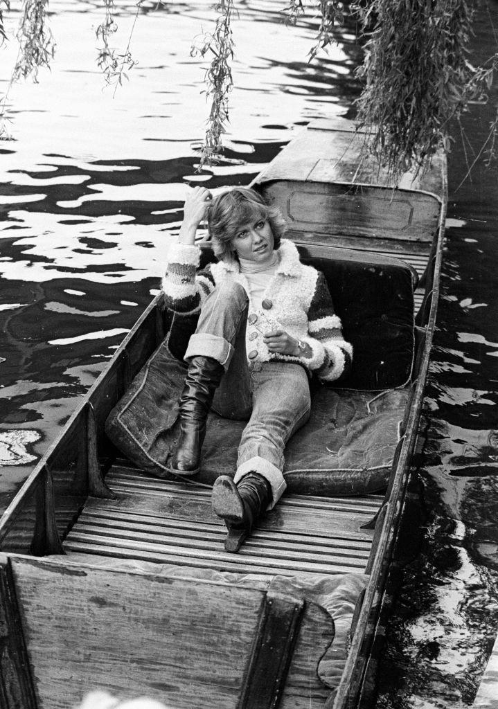 """<p>Olivia Newton-John relaxes on a canal boat, while filming her first music video for her single """"Follow Me"""" in 1975. </p>"""