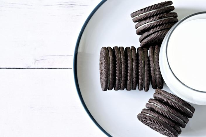 Top view of Oreo cookies in three horizontal stacks arranged around a glass of milk