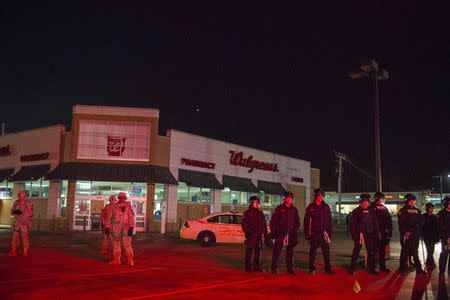 National Guard troops and police officers guard a Walgreens store from protesters during a second night of protests in Ferguson, Missouri November 25, 2014. REUTERS/Lucas Jackson