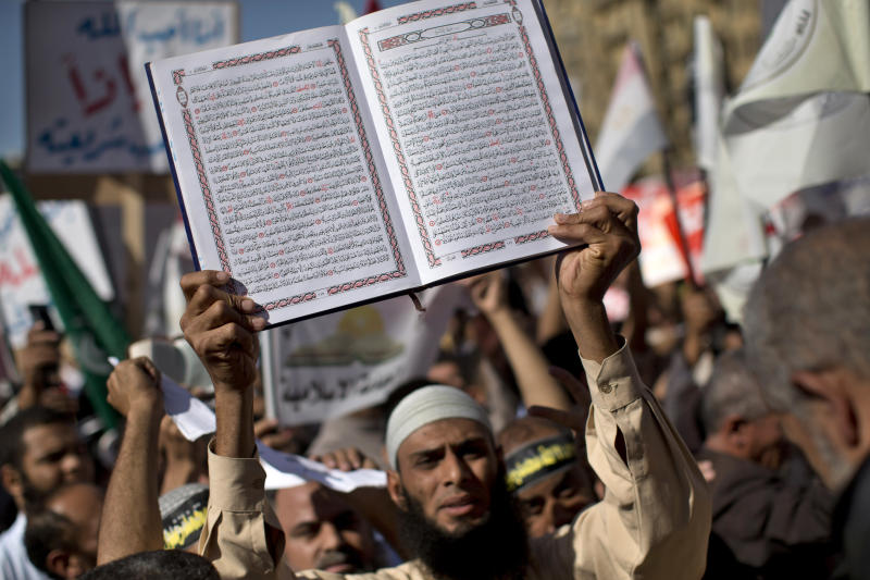 An Egyptian Muslim man holds the Quran, Islam's holy book, during a rally in Tahrir Square in Cairo, Friday, Nov. 9, 2012. Thousands of ultraconservative Muslims rallied in the Egyptian capital, demanding the country's new constitution be based on the rulings of Islamic law, or Shariah. (AP Photo/Bernat Armangue)