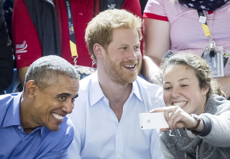 A woman takes a selfie with Obama and Prince Harry at the 2017 Invictus Games. (Danny Lawson - PA Images via Getty Images)