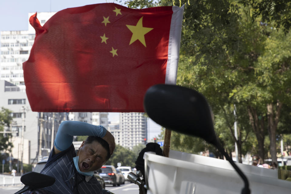 "A delivery man yawns near a national flag in Beijing on Wednesday, Sept. 2, 2020. China's Ministry of Commerce on Saturday, Sept. 19 2020 issued regulations for its ""unreliable entity"" list, aimed at foreign companies it says endanger its national sovereignty, security or development interests. (AP Photo/Ng Han Guan)"