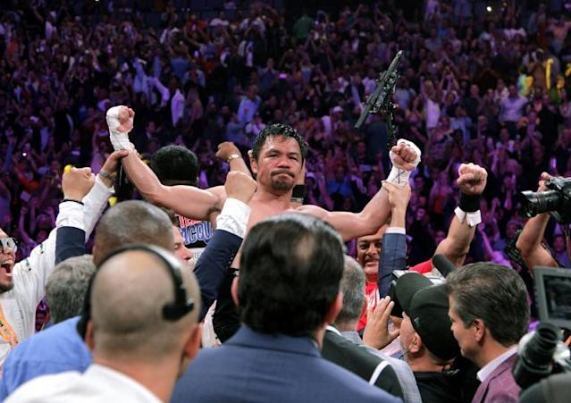 Filipino boxer Manny Pacquiao (C) celebrates after beating US boxer Keith Thurman in a WBA super world welterweight title fight in Las Vegas in July 2019 (AFP Photo/John Gurzinski)