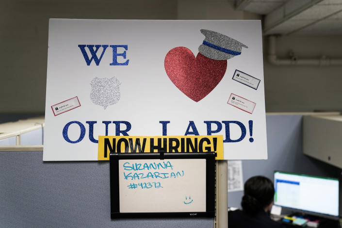 """In this Sept. 9, 2020, photo a """"Now Hiring"""" sign is placed on a cubicle wall in the office of the Los Angeles Police recruitment and employment division in Los Angeles. (AP Photo/Jae C. Hong)"""