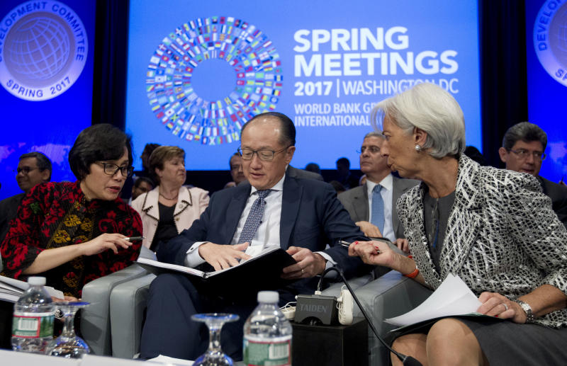 From left, Development Committee Chair and Indonesian Finance Minister Sri Mulyani Indrawati, World Bank President Jim Yong Kim, and International Monetary Fund (IMF) Managing Director Christine Lagarde confer before the Development Committee plenary during the World Bank/IMF Spring Meetings at IMF headquarters in Washington, on Saturday, April 22, 2017. (AP Photo/Jose Luis Magana)