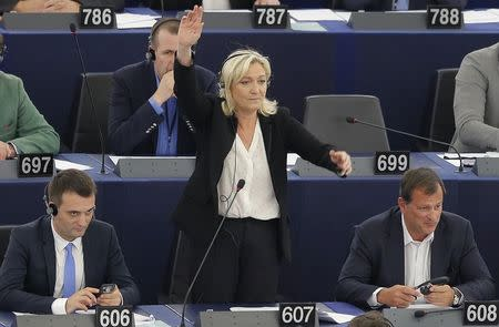 France's far-right National Front political party leader and MEP Marine Le Pen stands between fellow MEP Philippot and her companion Aliot as she asks for parole during a voting session at the European Parliament in Strasbourg