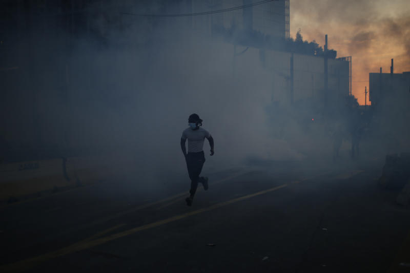 A protester runs through tear gas during a Paris demonstration on Tuesday. Source: AP
