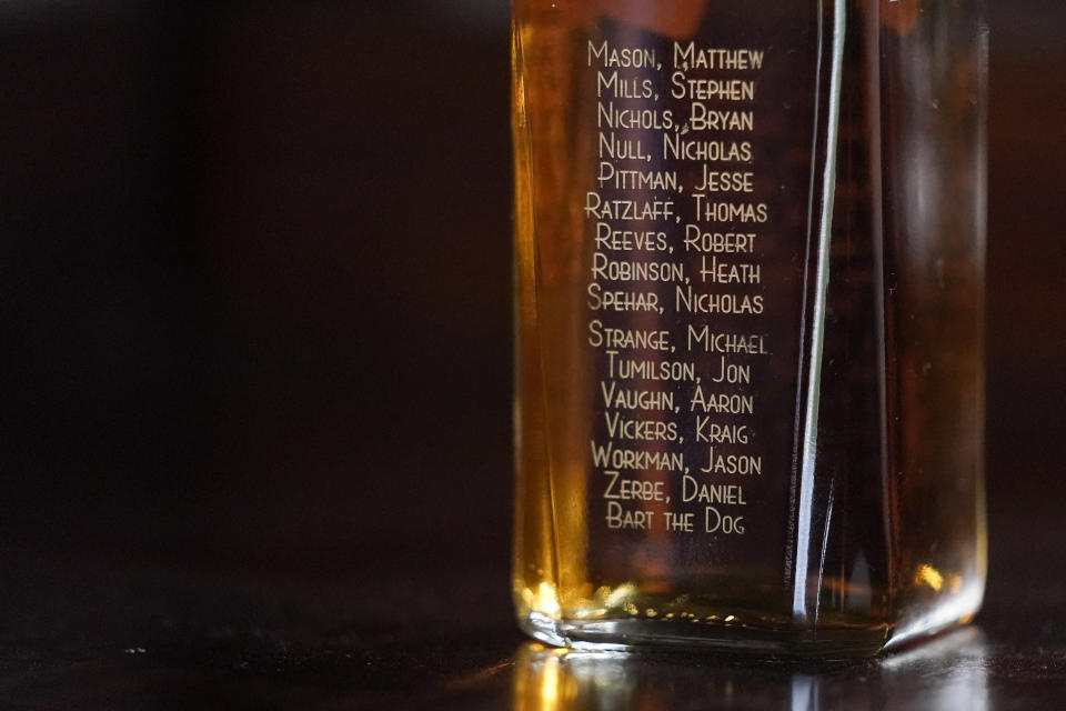 The names of servicemen who died when their Chinook helicopter was shot down in 2011 in Afghanistan are seen on a liquor bottle displayed by U.S. Army veteran Andrew Brennan, 36, in his home in Baltimore, on June 30, 2021. The former Army captain who flew combat missions in Afghanistan lost one of his closest friends, pilot Bryan Nichols, who was killed along with the entire crew when their Chinook helicopter was shot down in 2011, killing 30 Americans, seven Afghan soldiers and one interpreter. It was the single deadliest day for U.S. troops during the war. (AP Photo/Julio Cortez)