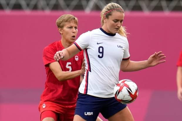 Canada's Quinn, left, and Lindsey Horan of the United States battle for the ball during their semifinal soccer match at Tokyo 2020 at Kashima Stadium on Monday. (Fernando Vergara/The Associated Press - image credit)