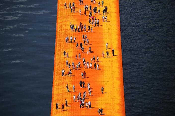 People walk on the 'The Floating Piers' installation on Lake Iseo in northern Italy (AFP Photo/Marco Bertorello)