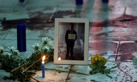 A portrait of Rodrigo Quintana, who was killed last night by a rubber bullet fired by the police in the headquarters of the Liberal Party after clashes, is placed next to his bloodstains in Asuncion