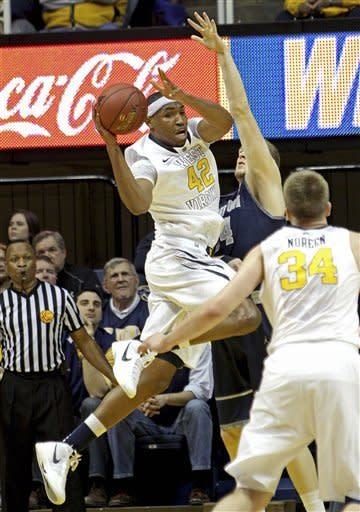West Virginia's Kevin Jones (42) looks to pass while guarded by Georgetown's Nate Lubick, center, in the first half of an NCAA college basketball game at WVU Coliseum in Morgantown, W.Va., on Saturday, Jan. 7, 2012. (AP Photo/David Smith)