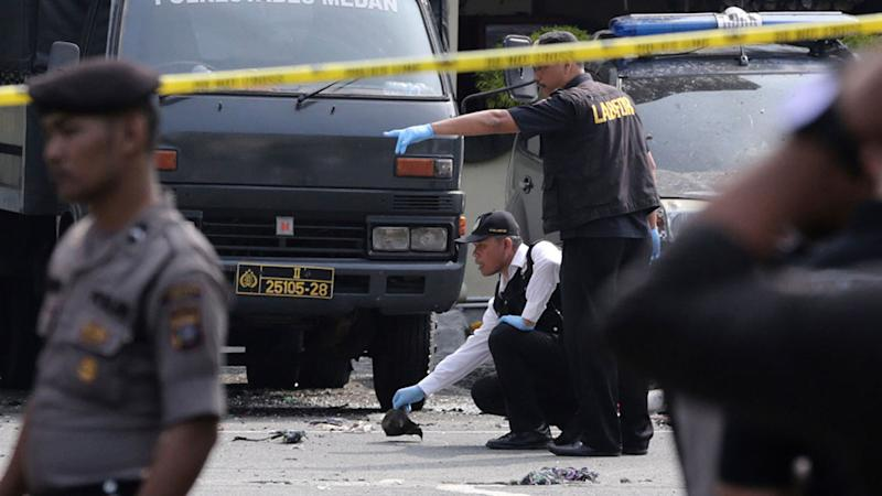 Picture of members of police forensic team inspecting the site of a bombing attack at the local police headquarters in Medan, North Sumatra, Indonesia, on Wednesday.