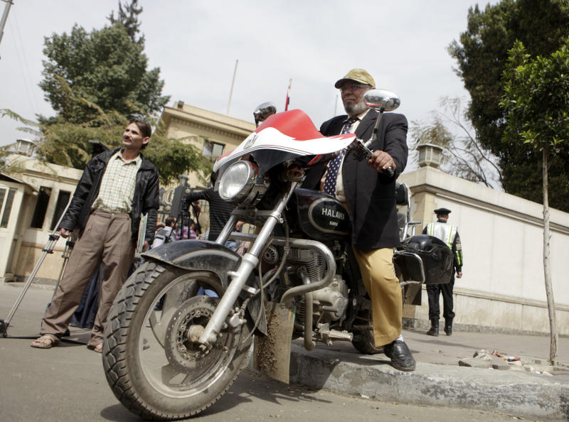 Egyptian presidential hopeful El-Sayyed Ahmed, left, stands as presidential hopeful Aboul Seoud Nourdeddine drives his motorbike painted with colors of the Egyptian national flag after they register their names for the upcoming presidential elections in Cairo, Egypt, Sunday, March 11, 2012. Politicians from the era of deposed president Hosni Mubarak, ex-military officers, and moderate and hardline Islamists are expected to become the front-runners in a vote that is scheduled to start May 23. (AP Photo/Amr Nabil)
