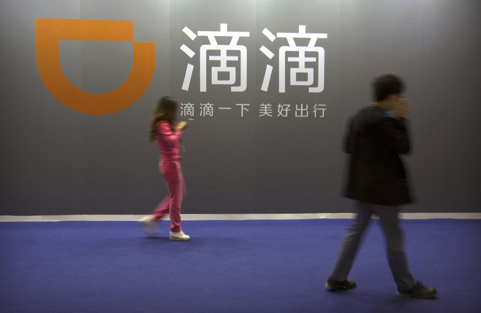 FILE - In this April 27, 2017, file photo, visitors walk past a sign for Chinese ride-hailing service Didi Chuxing at the Global Mobile Internet Conference (GMIC) in Beijing. China's internet watchdog said Friday, July 2, 2021 that it has launched an investigation into ride-hailing company Didi Global Inc. to protect national security and public interest, days after the company went public in New York. (AP Photo/Mark Schiefelbein,File)