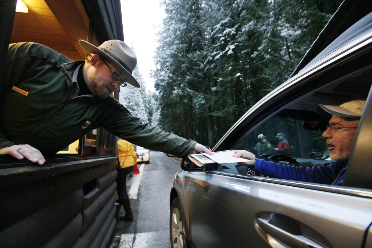 Mount Rainier National Park Ranger Matt Chalup, left, hands park information to one of the first visitors to the park at the Nisqually entrance Saturday morning, Jan. 7, 2012, near Ashford, Wash. The park opened for the first time since the shooting death of Ranger Margaret Anderson on Jan. 1. A memorial service for Anderson will be Tuesday, Jan. 10, in Tacoma, Wash. (AP Photo/Elaine Thompson)