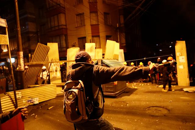 A protester against Bolivia's President Evo Morales uses a slingshot during clashes with government supporters in La Paz, Bolivia Nov. 7, 2019. (Photo: Kai Pfaffenbach/Reuters)