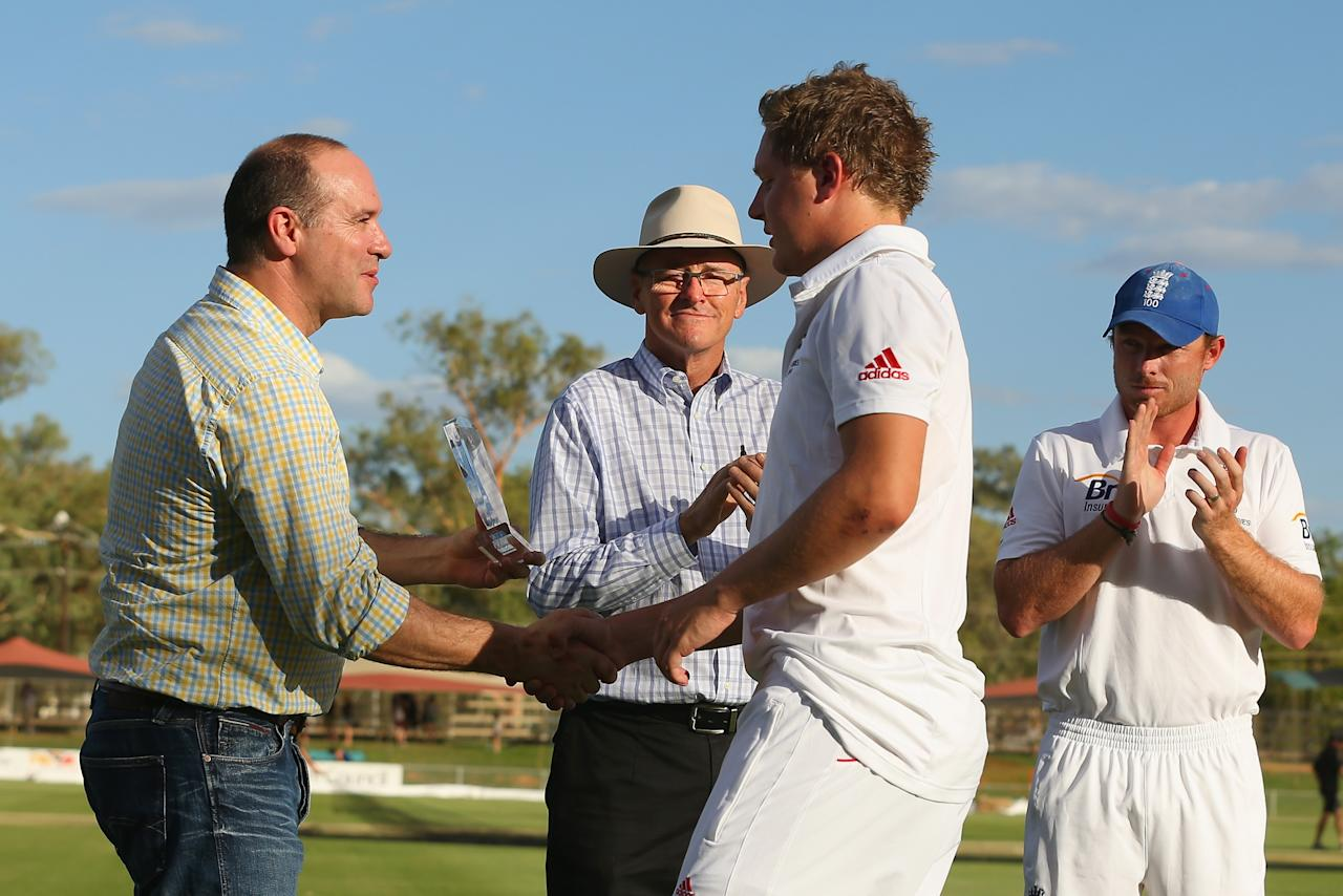 ALICE SPRINGS, AUSTRALIA - NOVEMBER 30:  The honourable Matthew Conlan, Minister for Sport, Recreation and Racing, Minister for Tourism presents Gary Ballance of England with the player of the match trophy during the end of match presentation after day two of the tour match between the Chairman's XI and England at Traeger Park Oval on November 30, 2013 in Alice Springs, Australia.  (Photo by Mark Kolbe/Getty Images)