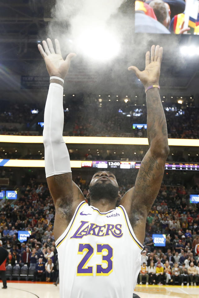 Los Angeles Lakers forward LeBron James (23) flings powder in the air before the start of the first half during an NBA basketball game against the Utah Jazz Wednesday, Dec. 4, 2019, in Salt Lake City. (AP Photo/Rick Bowmer)