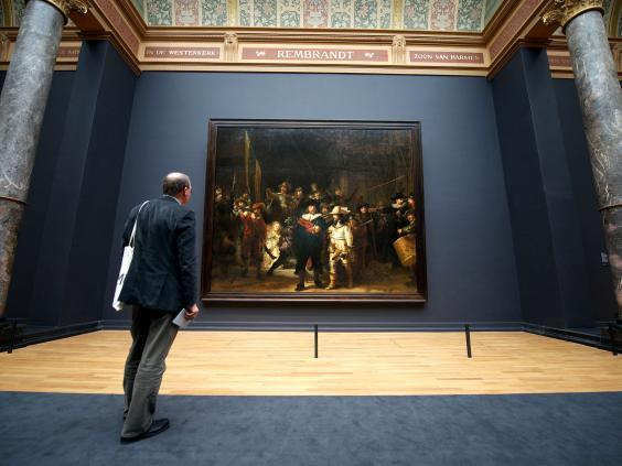 A visitor admires Rembrandt's masterpiece 'The Night Watch' in Amsterdam's Rijkmuseum (AFP/Getty)