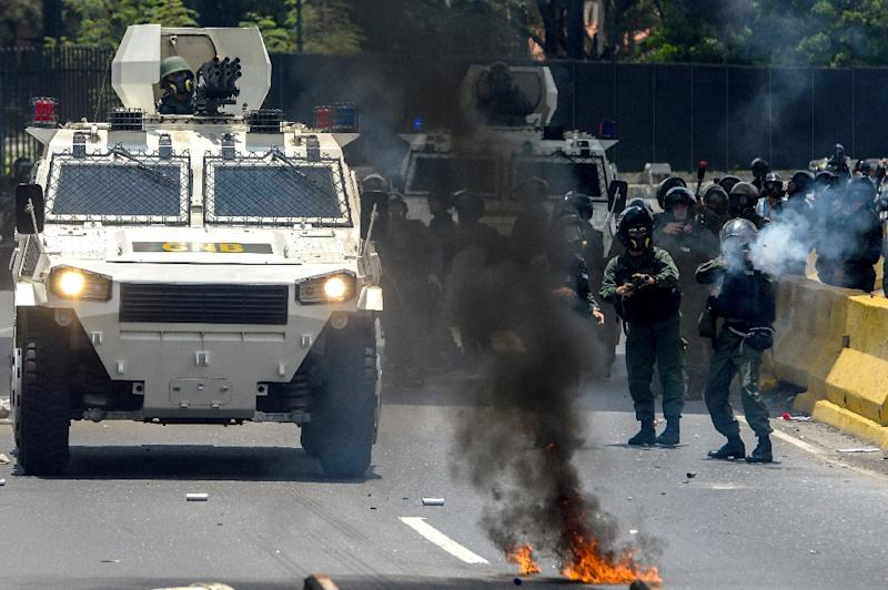 Venezuelan National Guard personnel in riot gear and opposition activists clash in Caracas on April 10, 2017 (AFP Photo/FEDERICO PARRA)