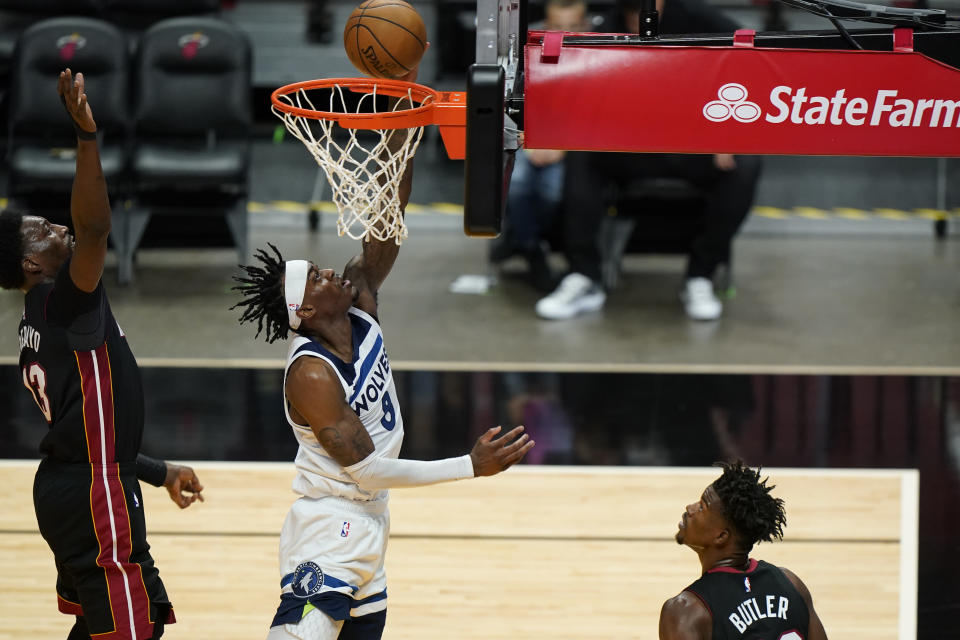 Minnesota Timberwolves forward Jarred Vanderbilt (8) goes up to shoot against Miami Heat center Bam Adebayo (13) as Heat forward Jimmy Butler looks on during the first half of an NBA basketball game, Friday, May 7, 2021, in Miami. (AP Photo/Wilfredo Lee)