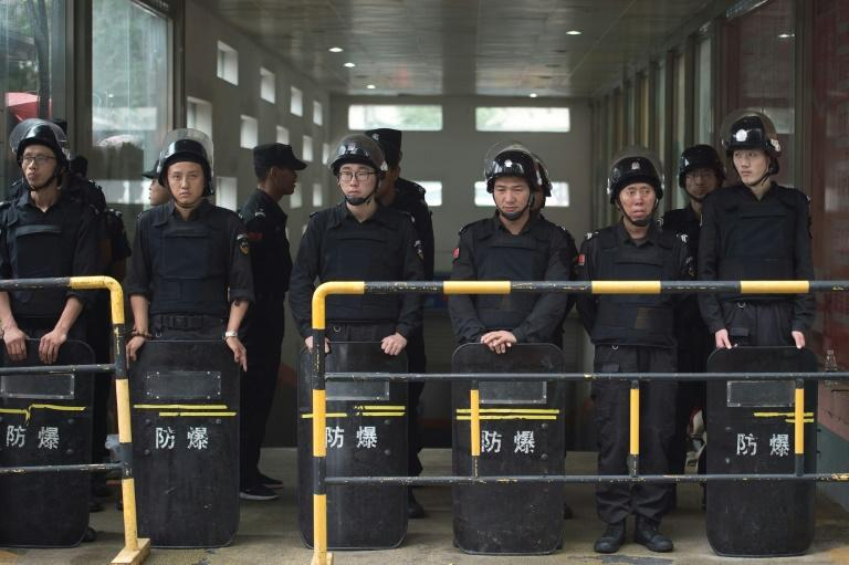 Riot police officers stand guard outside the Beijing Zoo wholesale market in Beijing