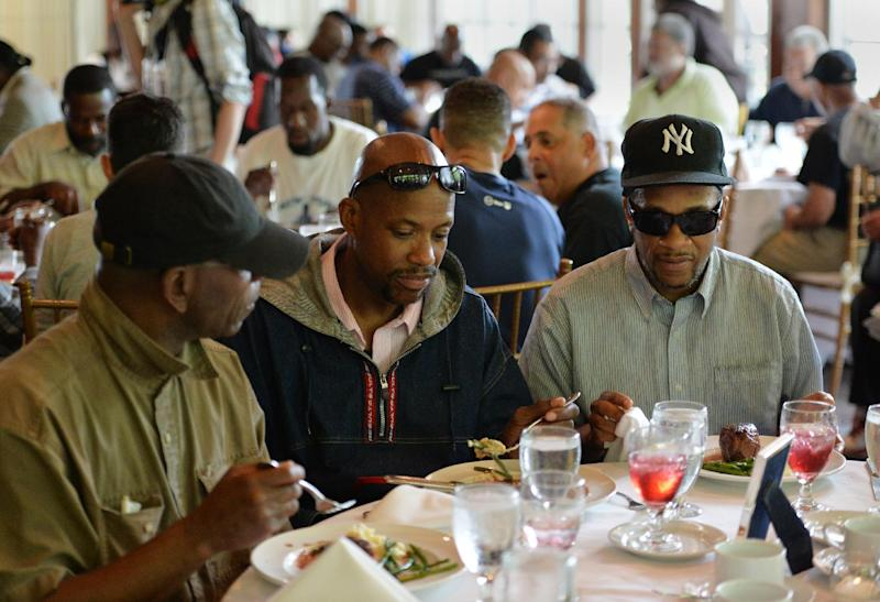 Homeless men sit down to eat at a luncheon hosted by Chinese philanthropist Chen Guangbiao for several hundred homeless people from the New York City Rescue Mission June 25, 2014 at The Boathouse restaurant in New York's Central Park (AFP Photo/Stan Honda)