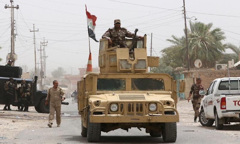 An Iraqi security forces member stands on a Hummer in the town of Baiji, as allied forces fight against the Islamic State jihadist group to try to retake the strategic town on July 2, 2015