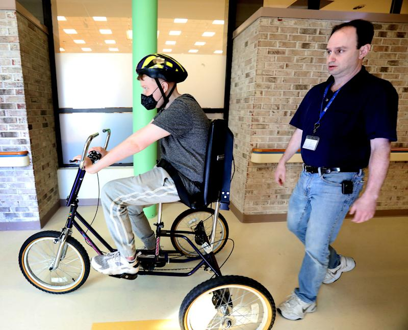 Mark Felsenfeld, PT watches as Zachary Losee rides a bike to help build up his stamina at Blythedale Children's Hospital Feb. 5, 2019. Zach, a heart transplant recipient wants to become an organ donor advocate after getting a new heart.
