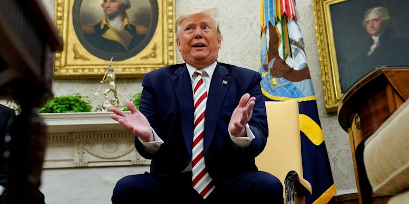 FILE PHOTO: U.S. President Donald Trump answers questions from reporters sitting in front of former U.S. presidents George Washington and Thomas Jefferson as he meets with Romania's President Klaus Iohannis in the Oval Office of the White House in Washington, U.S. August 20, 2019. REUTERS/Kevin Lamarque/File Photo