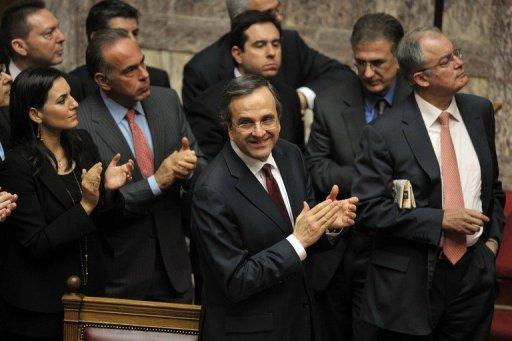 Greek PM Antonis Samaras (C) and his ministers applaud after Greek lawmakers approved the 2013 budget