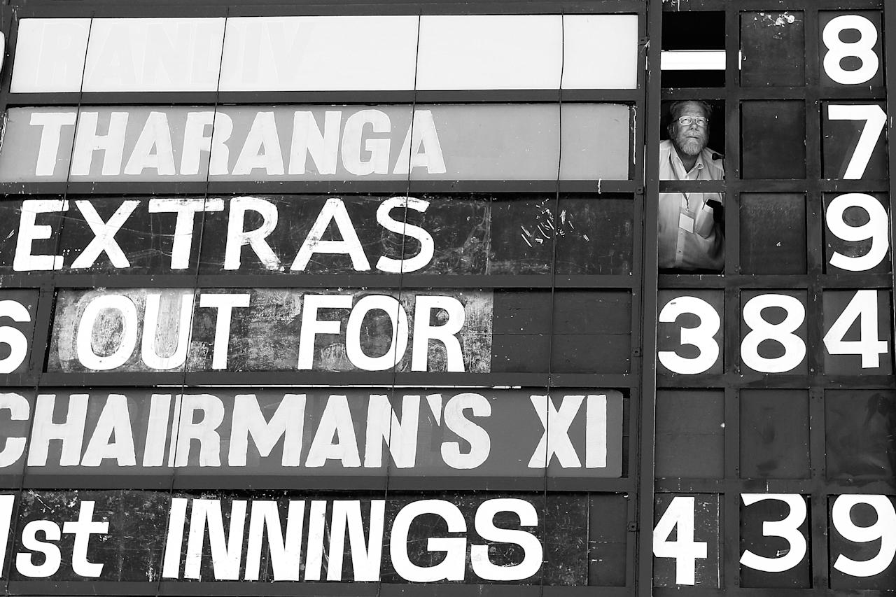 CANBERRA, AUSTRALIA - DECEMBER 08:  (EDITORS NOTE: Image has been converted to Black & White) A scoreboard operator watches play during an international tour match between the Chairman's XI and Sri Lanka from inside The Jack Fingleton Scoreboard at Manuka Oval on December 8, 2012 in Canberra, Australia. The Jack Fingleton Scoreboard was first erected at the MCG in 1901. In 1982 it was replaced by an electronic board and donated to the Manuka Oval by the Melbourne Cricket Club as memorial to J.H.W Fingleton OBE.  (Photo by Brendon Thorne/Getty Images)
