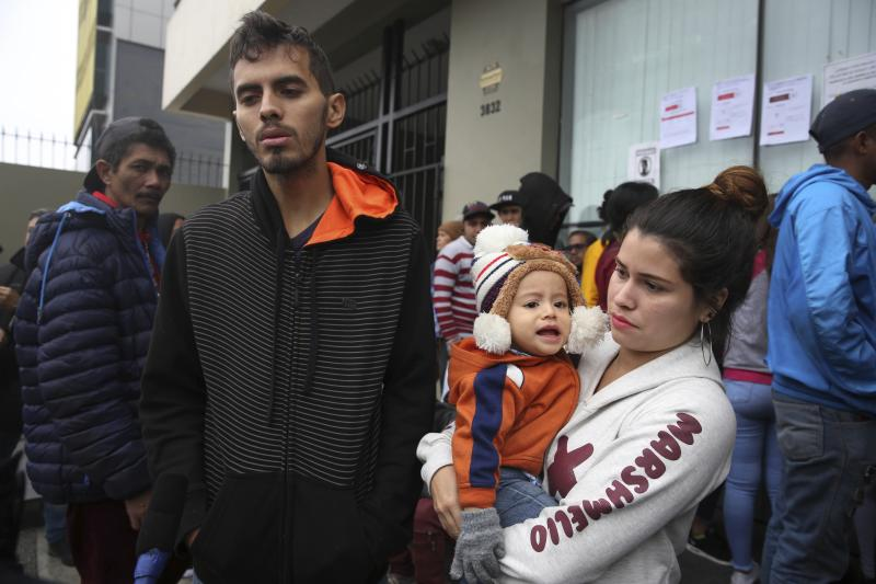 Venezuelan migrant couple Johan Alvarez and Daniela Tovar, with their son Matias, speak during an interview outside a refugee office run by Peru's Special Commission for Refugees Executive Secretariat, where they wait to apply for refugee status in Lima, Peru, Tuesday, June 18, 2019. When Alvarez, 25, was unable to provide more than one meal a day for his young family he knew it was time to leave Venezuela. In Peru he works at a candle factory and is able to provide three meals a day. (AP Photo/Martin Mejia)