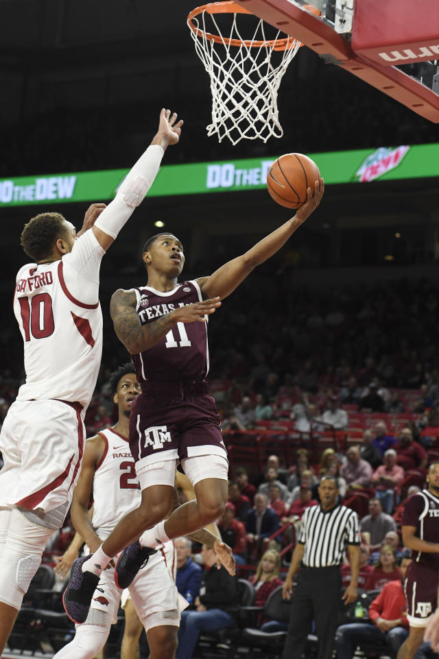 Texas A&M guard Wendell Mitchell (11) drives past Arkansas defender Daniel Gafford (10) during the second half of an NCAA college basketball game, Saturday, Feb. 23, 2019, in Fayetteville, Ark. (AP Photo/Michael Woods)