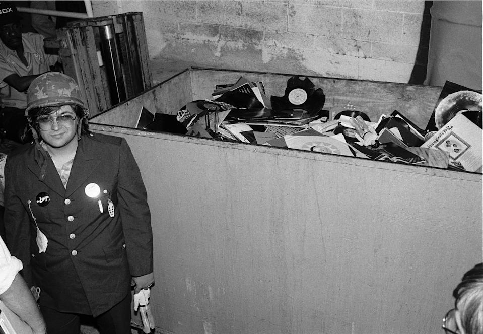 American disc jockey (from WLUP radio, 'The Loop') Steve Dahl stands beside of a crate full of unwanted disco records collected during an anti-disco promotion at Comiskey Park, Chicago, Illinois, July 12, 1979. The event, hosted by Dahl and held between games of a doubleheader between the Chicago White Sox and the Detroit Tigers, allowed fans to attend the games for 98 cents along with an unwanted record and, following the detonation of those records, eventually resulted in the White Sox forfeiture of the second game due to unsafe playing conditions when fans stormed the field causing serious damage to the venue and playing surface. (Photo: Paul Natkin/Getty Images)