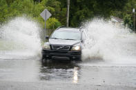 A vehicle splashes runoff water from Tropical Storm Claudette, Saturday, June 19, 2021, in downtown Biloxi, Miss. Although flooding was minor in this neighborhood, some drivers encountered pools they needed to drive through. (AP Photo/Rogelio V. Solis)