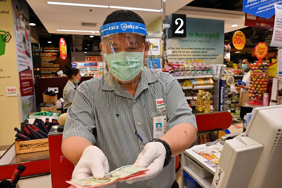 A cashier wearing a face mask and rubber gloves, as a preventive measure against COVID-19 coronavirus, attends to customers at a grocery in Bangkok on March 30, 2020. (Photo by Romeo GACAD / AFP) (Photo by ROMEO GACAD/AFP via Getty Images)