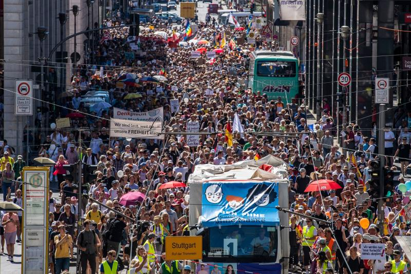 "Thousands of demonstrators march down the Friedrichstrasse street as they take part in a demonstration by the initiative ""Querdenken-711"" with the slogan ""the end of the pandemic-the day of freedom"" to protest against the current measures to curb the spread of the Coronavirus, in Berlin, on August 1, 2020. (Photo by John MACDOUGALL / AFP) (Photo by JOHN MACDOUGALL/AFP via Getty Images)"