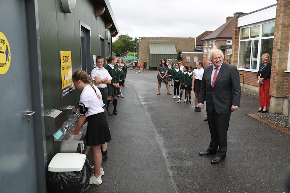 BOVINGDON, ENGLAND - JUNE 19: Prime Minister Boris Johnson waits in line in the playground to wash his hands during a visit to Bovingdon Primary School on June 19, 2020 near Hemel Hempstead. The Government have announced a GBP 1 billion plan to help pupils catch up with their education before September after spending months out of school during the coronavirus lockdown. (Photo by Steve Parsons - WPA Pool/Getty Images)