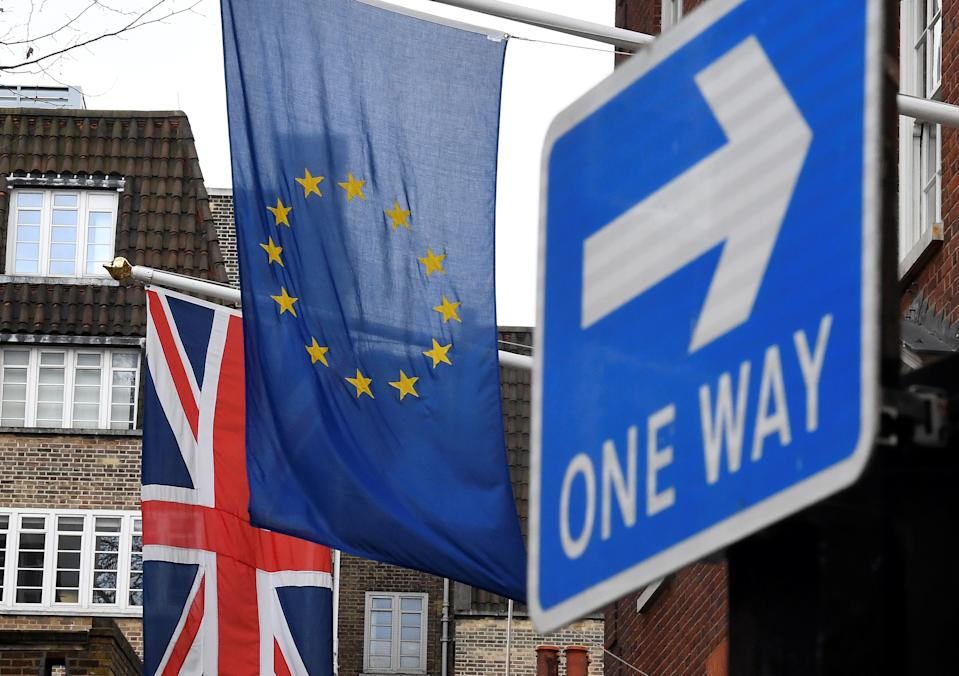 The British union flag and the EU flag are seen hanging outside of a building near a traffic direction sign in London. Photo: REUTERS/Toby Melville