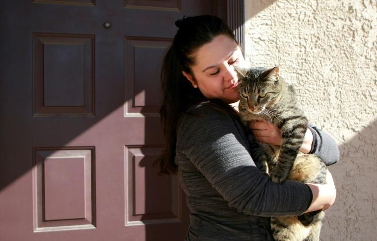 Bartender Jessie Klenke, who is out of work due to the COVID-19 pandemic, hugs her cat Tito outside her home in Las Vegas