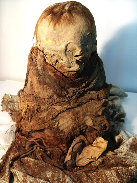 This undated photo released by Peru's Ministry of Culture shows a mummy. The mummified toddler seized from antiquities traffickers is at least 700 years old and sits about a foot tall, according to authorities. On Tuesday, Nov. 6, 2012, it was returned to Peru by Bolivia, where officials seized it two years ago when smugglers tried to ship it to France. (AP Photo/Peruvian Ministry of Culture)