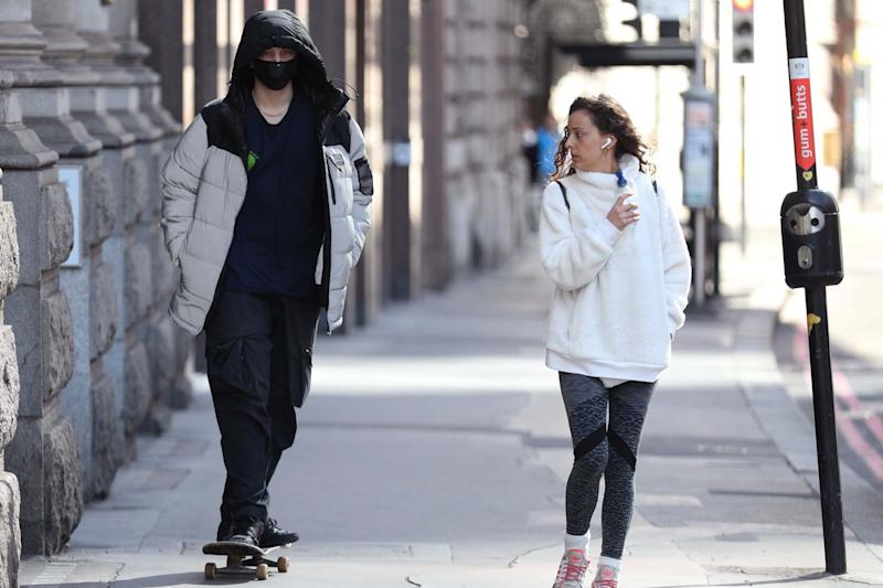 A skateboader wearing a face mask in the City of London: PA
