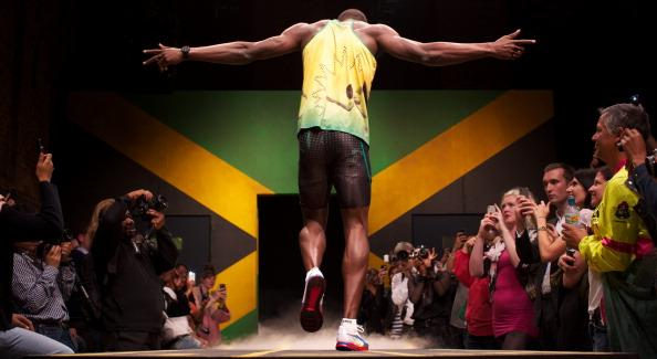 Jamaican sprinter Usain Bolt walks on a podium during the official presentation of the Jamaican clothing for the 2012 Olympic games, in London, on June 1, 2012.  AFP PHOTO / ANDREW COWIE        (Photo credit should read Andrew Cowie/AFP/GettyImages)